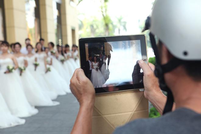 Sự xuất hiện của nhiều cặp đôi trong trang phục cưới khiến người dân thành phố thích thú đứng xem.