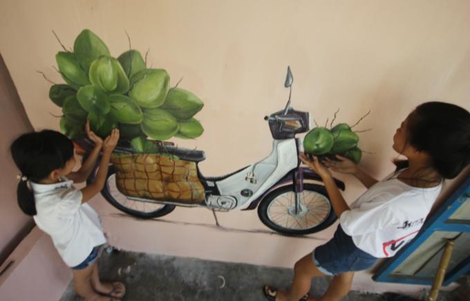 Các em nhỏ cũng rất thích thú với các bức tranh bích họa sinh động