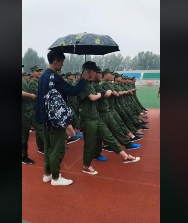 cầm ô che cho bạn gái, xôn xao clip chàng trai che ô cho bạn gái tập quân sự